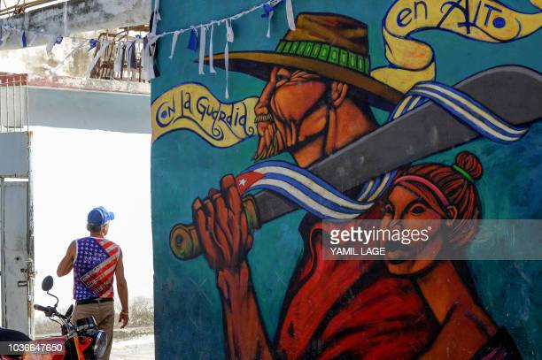 A Cuban man wearing a Tshirt with the US flag stands near a graffiti in Havana on September 20 2018 The Cuban Chancellor Bruno Rodriguez recieved in...