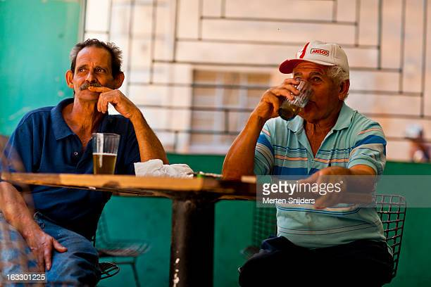 cuban men at bar table drinking beer - merten snijders stock pictures, royalty-free photos & images