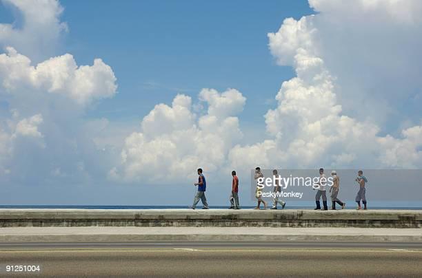 Cuban Men Walk Along the Malecon Sea Wall Havana Cuba