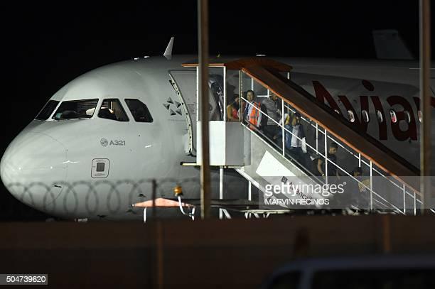 Cuban migrants arrive at the Monsignor Oscar Romero International Airport in San Luis Talpa, 44 km south of San Salvador on January 12, 2016. A group...