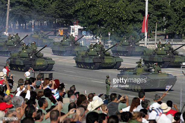 Cuban military drive their tanks during a parade through Havana's Revolution Square to mark the 50th anniversary celebration of the forming of Cuba's...
