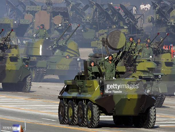 Cuban military drive their vehicles during a parade through Havana's Revolution Square to mark the 50th anniversary celebration of the forming of...