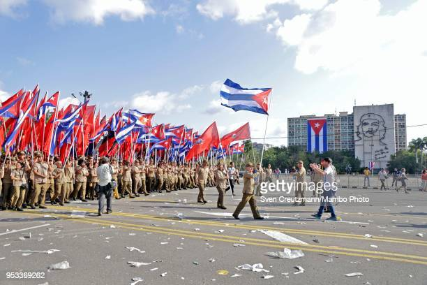 Cuban military personnel carry Cuban flags as they pass in front of the image of Che Guevara at the Ministry of Interior building as closing the...