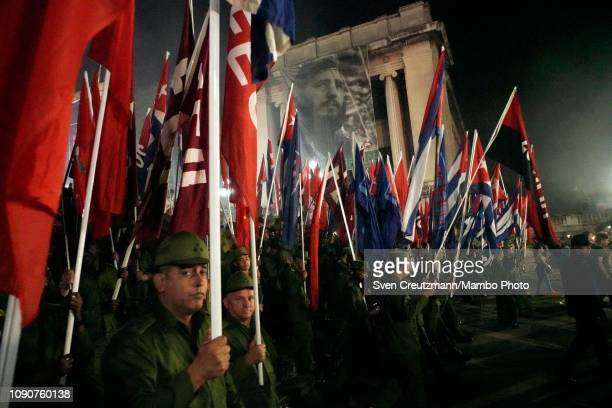 Cuban military personnel carry flags and torches as they walk under a giant photo of late Revolution leader Fidel Castro during a march at the...