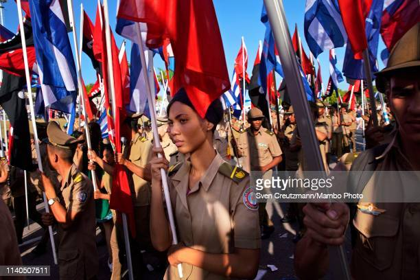 Cuban military personnel carry flags as they march during the May Day parade at the Revolution square on May 1st in Havana Cuba The march takes place...