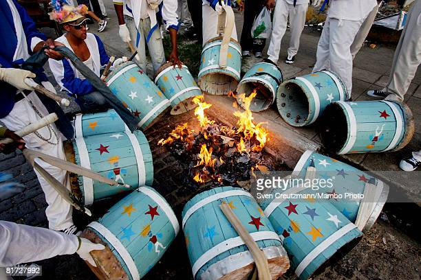 Cuban musicians warm up their drums at an open fire during the Camaguey carnival June 25 2008 in Camaguey Cuba The first day celebration of the...