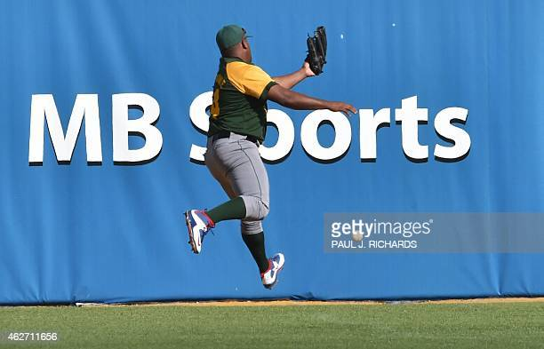 Cuban National baseball team leftfielder Alfredo Despaigne misses a long fly to center field off the bat of Dominican National baseball team...