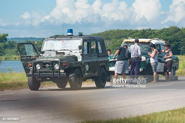 Cuban National Police or PNR jeep stopped by an old American car in the highway from Havana to Pinar del Rio