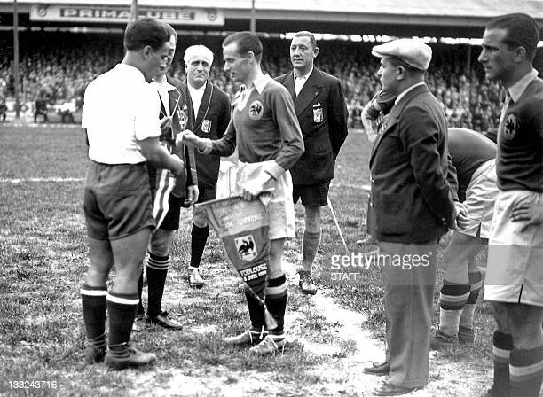 Cuban national soccer team captain Manuel Chorens exchanges pennants with his Romanian counterpart Gheorghe Rasinaru before the start of the World...