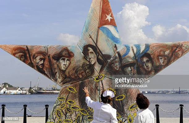 Cuban nurses look at a starshaped work depicting revolutionaries on display in Havana's Bay on January 13 during an art exhibition in the framework...