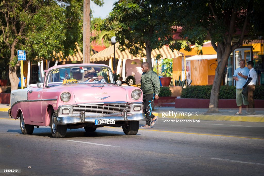 Cuban old cars in action: Driver of an open-top pink taxi ...