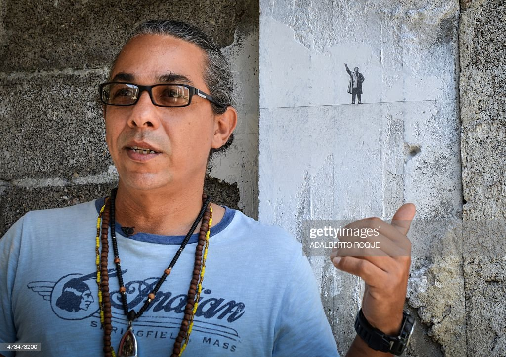 Cuban painter Glexis Novoa speaks as he works on a wall in a old building in Havana, on May 15, 2015. After being censored in the 80s, Novoa emigrated to US where he lives. It is the first time he is invited to exhibit his work in Cuba.