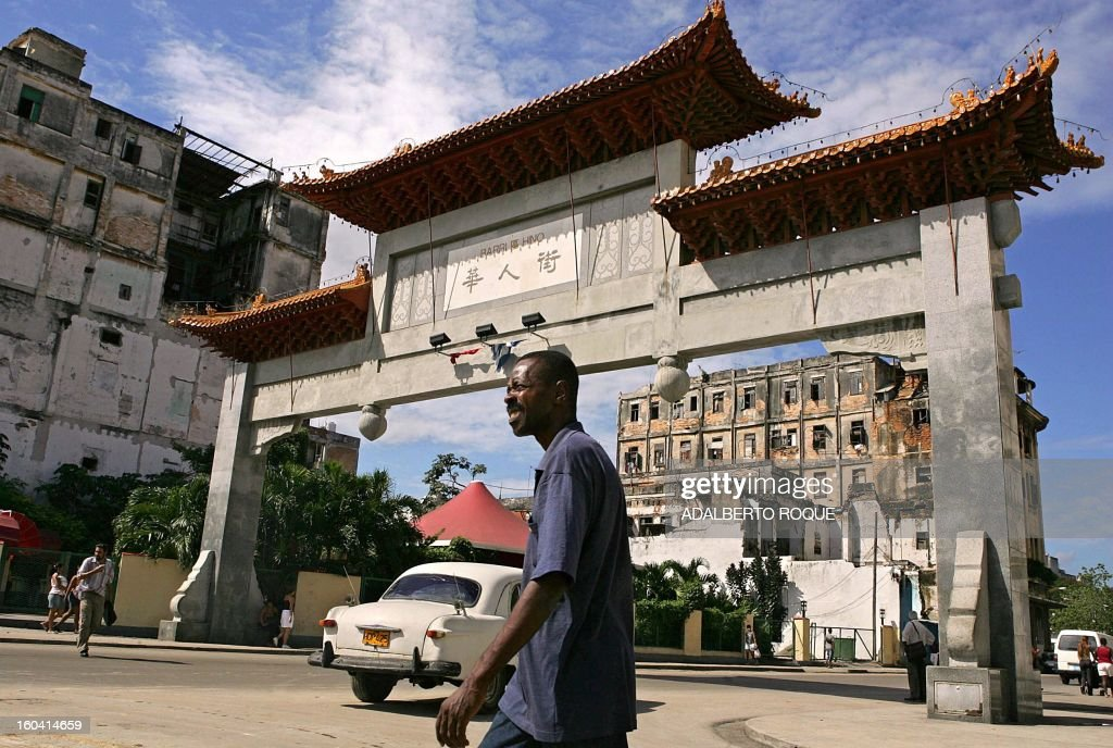 A Cuban passes in front of the Cuba-China friendship arch in Havana's Chinatown, 28 September 2005