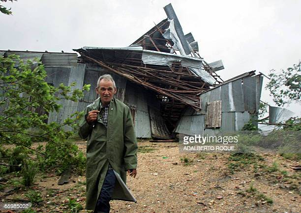 Cuban peasant walks in front of a destroyed tobacco warehouse 22 October 2005 in San Juan y Martinez province of Pinar del Rio due to storms...