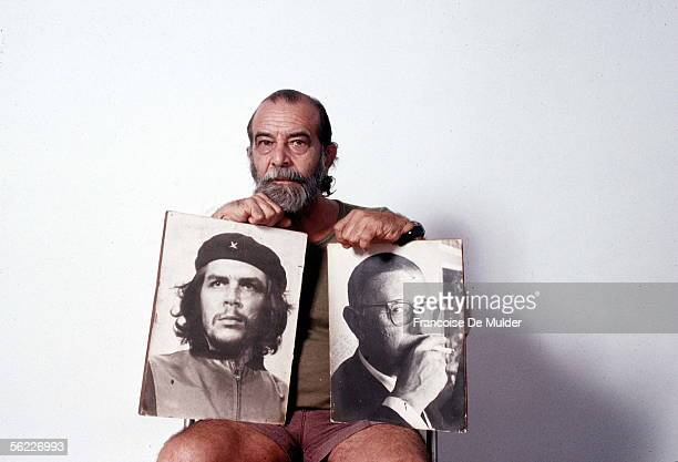 Cuban photographer Alberto Korda holding two of his works representing Che and JeanPaul Sartre Havana 1988
