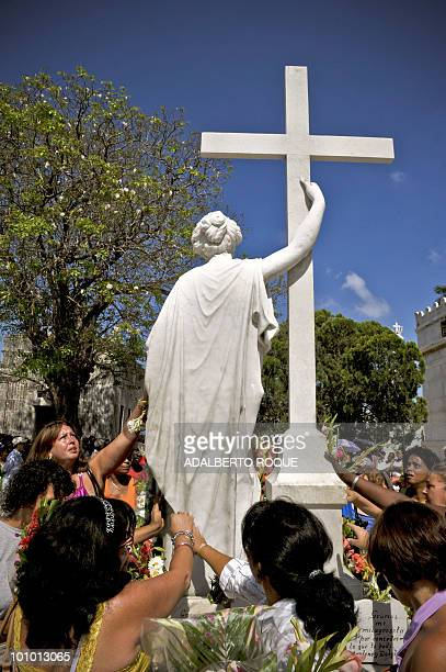 Cuban pilgrims touch the statue on the tomb of Amelia Goyri La Milagrosa May 27 2010 in Havana Every year scores of Cubans visit the grave of La...