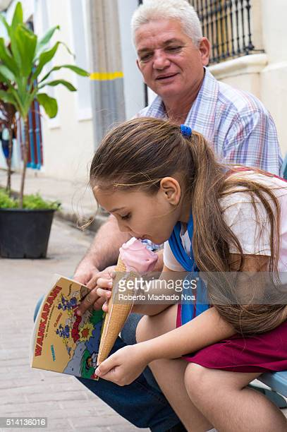 Cuban pioneer girl wearing uniform eating strawberry ice cream cone on the sidewalk
