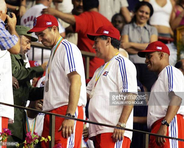 Cuban President Fidel Castro congratulates his son Antonio and other members of the Cuban baseball national team during a ceremony in Havana 21 March...