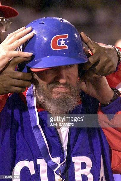 Cuban President Fidel Castro gets his helmet adjusted before a friendly baseball game against the Venezuelan team led by Venezuelan counterpart Hugo...