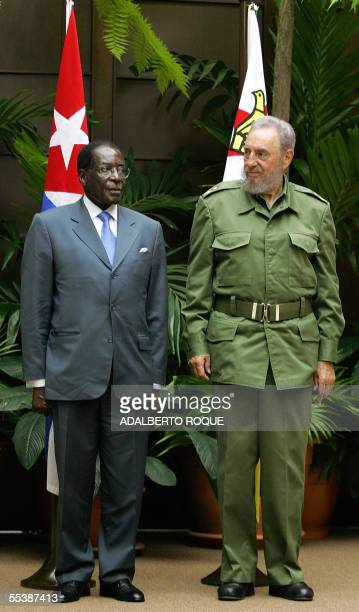 Cuban President Fidel Castro poses for an official picture with his Zimbabwean counterpart Robert Mugabe during a welcoming ceremony offered at the...