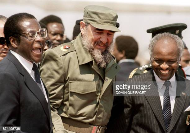 Cuban President Fidel Castro shares a laugh with Zimbabwean President Canaan Banana and Zimbabwean Prime minister Robert Mugabe as he arrives in...