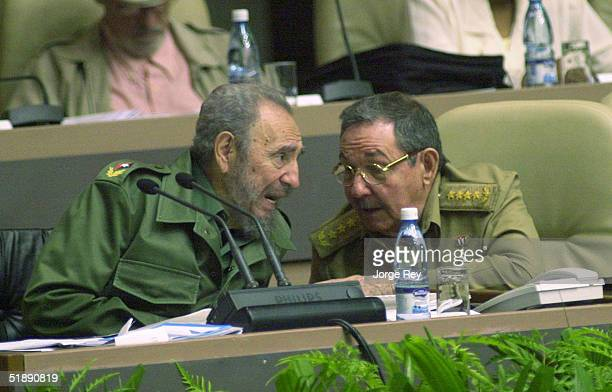 Cuban President Fidel Castro talks to his brother Raul Castro during the Cuban Parliament's session in the Palacio of the Conventions December 23...