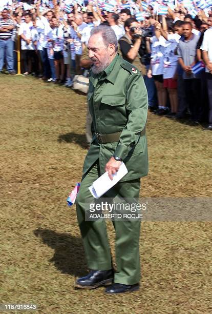 Cuban President Fidel Castro walks across grass 07 July on the outskirts of Havana during a political rally to condemn the sentences of five Cuban...