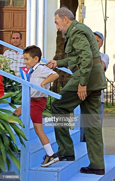 Cuban president Fidel Castro walks up a flight of stairs with Elian Gonzalez 14 July 2001 in Cardenas Cuba during a political gathering to inaugurate...