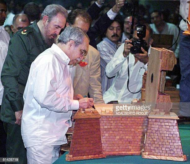 Cuban President Fidel Castro watches Colombian writer and Nobel Laureate for Literature Gabriel Garcia Marquez sign a special box for Cuban cigars...