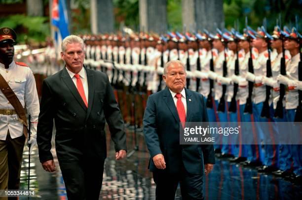 Cuban President Miguel DiazCanel and Salvadoran President Salvador Sanchez Ceren review a guard of honour during Sanchez's welcome ceremony at the...
