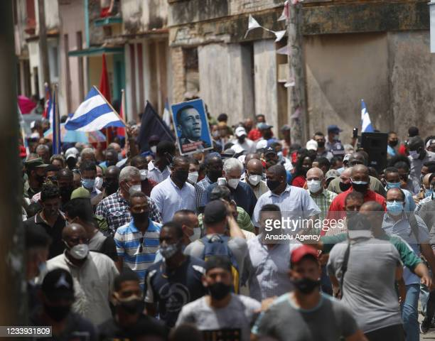 Cuban President Miguel Diaz-Canel walks alongside his supporters in the town of San Antonio de los Banos after the anti-government protests in which...