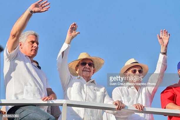Cuban President Raul Castro and Vice Presidents Miguel Diaz Canel and Jose Ramon Machado Ventura wave while observing a march celebrating workers day...