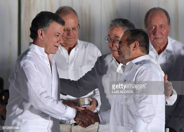 Cuban President Raul Castro greets Colombian President Juan Manuel Santos and the leader of the FARC Rodrigo Londono better known by his nom de...