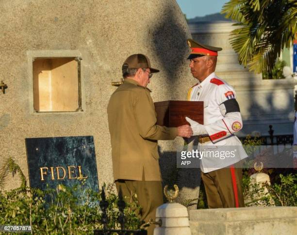 TOPSHOT Cuban President Raul Castro places the urn with the ashes of his brother Fidel Castro in his tomb at the Santa Ifigenia cemetery in Santiago...