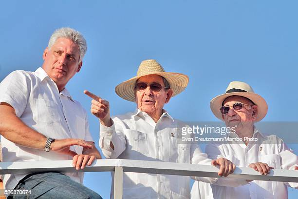 Cuban President Raul Castro points out as he talks to Vice Presidents Miguel Diaz Canel and Jose Ramon Machado Ventura while observing a march...