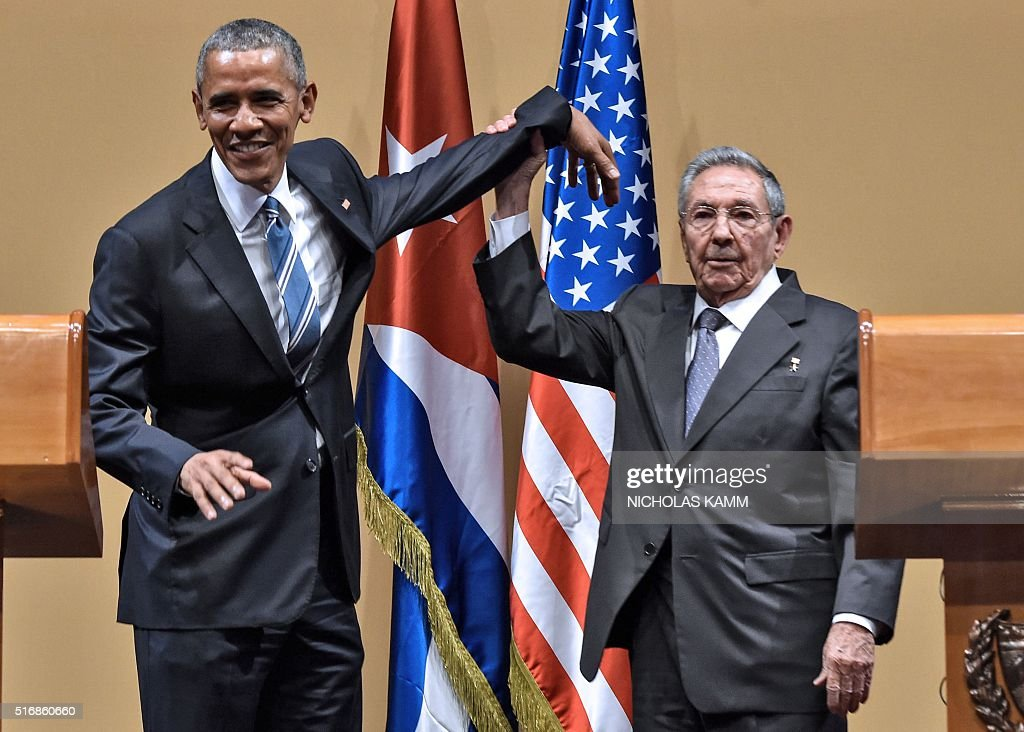 Cuban President Raul Castro (R) raises US President Barack Obama's hand during a meeting at the Revolution Palace in Havana on March 21, 2016. Cuba's Communist President Raul Castro on Monday stood next to Barack Obama and hailed his opposition to a long-standing economic 'blockade,' but said it would need to end before ties are fully normalized. AFP PHOTO/Nicholas KAMM / AFP / NICHOLAS