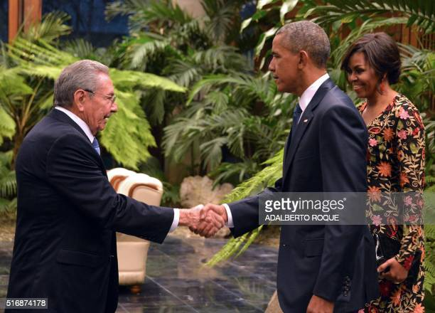 TOPSHOT Cuban President Raul Castro shakes hands with US President Barack Obama next to US First Lady Michelle Obama ahead of the state dinner at the...