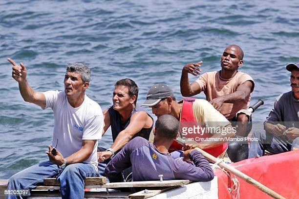 Cuban rafters talk with security officers after seven men failed in an attempt to leave the island at the Malecon waterfront on June 4 2009 in Havana...