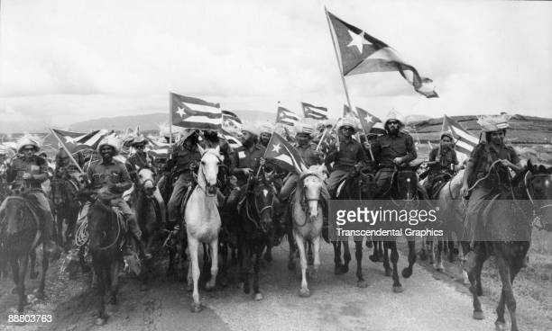 Cuban revolutionary Camilo Cienfuegos carries the large Cuban flag on the right while leading a group of campesinos through the coutryside as the end...