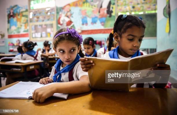 Cuban schoolgirls read during class on November 13 in Havana AFP PHOTO