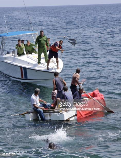 Cuban security officer throws an anchor toward a raft after seven men failed in an attempt to leave the island at the Malecon waterfront on June 4...