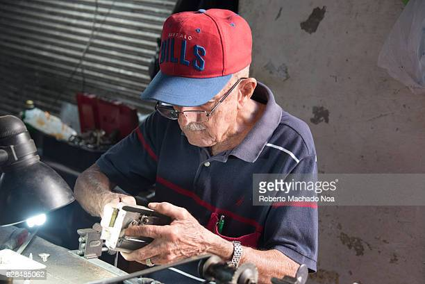 Cuban senior man fixing a door lock Self employment is now allowed in Cuba so many pensioners have returned to work owning their own stands