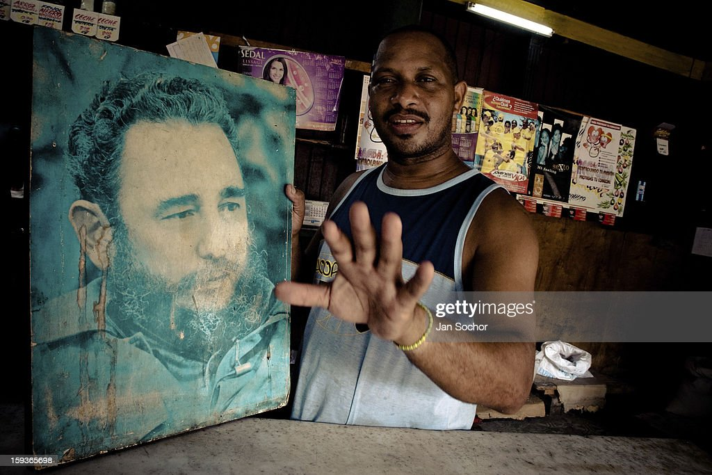 A Cuban shop assistant holds a large portrait photo of the revolutionary leader Fidel Castro, Havana, Cuba, on 20 August 2008 in Havana, Cuba. During the Cuban Revolution, an armed rebellion at the end of the 1950s in Cuba, most of the revolutionary leaders started as no-name soldiers fighting in the jungle. Although the revolutionary leaders, after taking over the power, became autocratic rulers holding almost absolute power and putting the opposition in jail, for some reason Cuban people have never stopped to worship Fidel Castro, Che Guevara, Raul Castro and others. Cubans hang their photos and portraits on the wall in homes, shops and working places even they don't have to. The people of Cuba love their heroes.