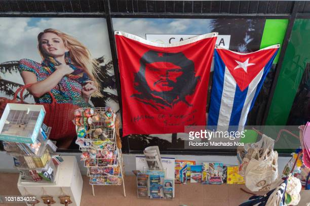 Cuban souvenirs with the Che Guevara image in a red cloth The image highly contrast with an advertisement in the store glass