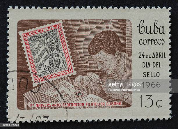 Cuban stamp commemorating the 1st anniversary of the Cuban philatelic federation A man is looking through a magnifying glass at his stamp collection...