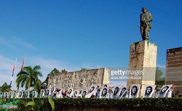 Cuban students hold banners with the image of revolutionary leader Ernesto 'Che' Guevara during the official ceremony to commemorate the 40th...