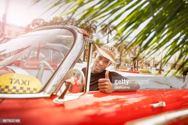 Cuban taxi driver giving Ok sign driving vintage car in Cuba Old Havana