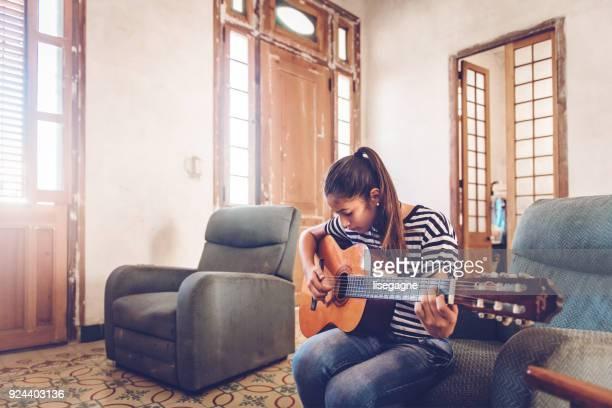 cuban teenager playing guitar - cuba girls stock pictures, royalty-free photos & images