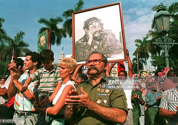 Cuban veteran joins other Cubans holding up portraits of their leader Fidel Castro 01 May for May Day celebrations in the old HavanaCuba Fidel Castro...