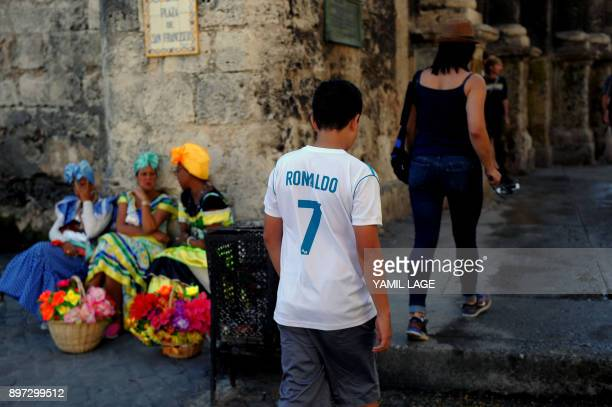 A Cuban wearing a jersey of Spain's football team Real Madrid walks along the street in Havana on the eve of huge El Clasico clash against Barcelona...